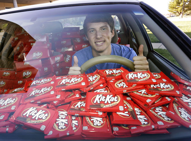 IMAGE DISTRIBUTED FOR THE HERSHEY COMPANY - Hunter Jobbins, freshman at Kansas State University, is all smiles in his car filled with nearly 6,500 Kit Kat bars on Thursday, Nov. 3, 2016, in Manhattan, Kansas. Earlier this week, Jobbins had a Kit Kat bar stolen from his unlocked car and a mysterious note was left from the thief. (Colin E. Braley/AP Images for The Hershey Company)
